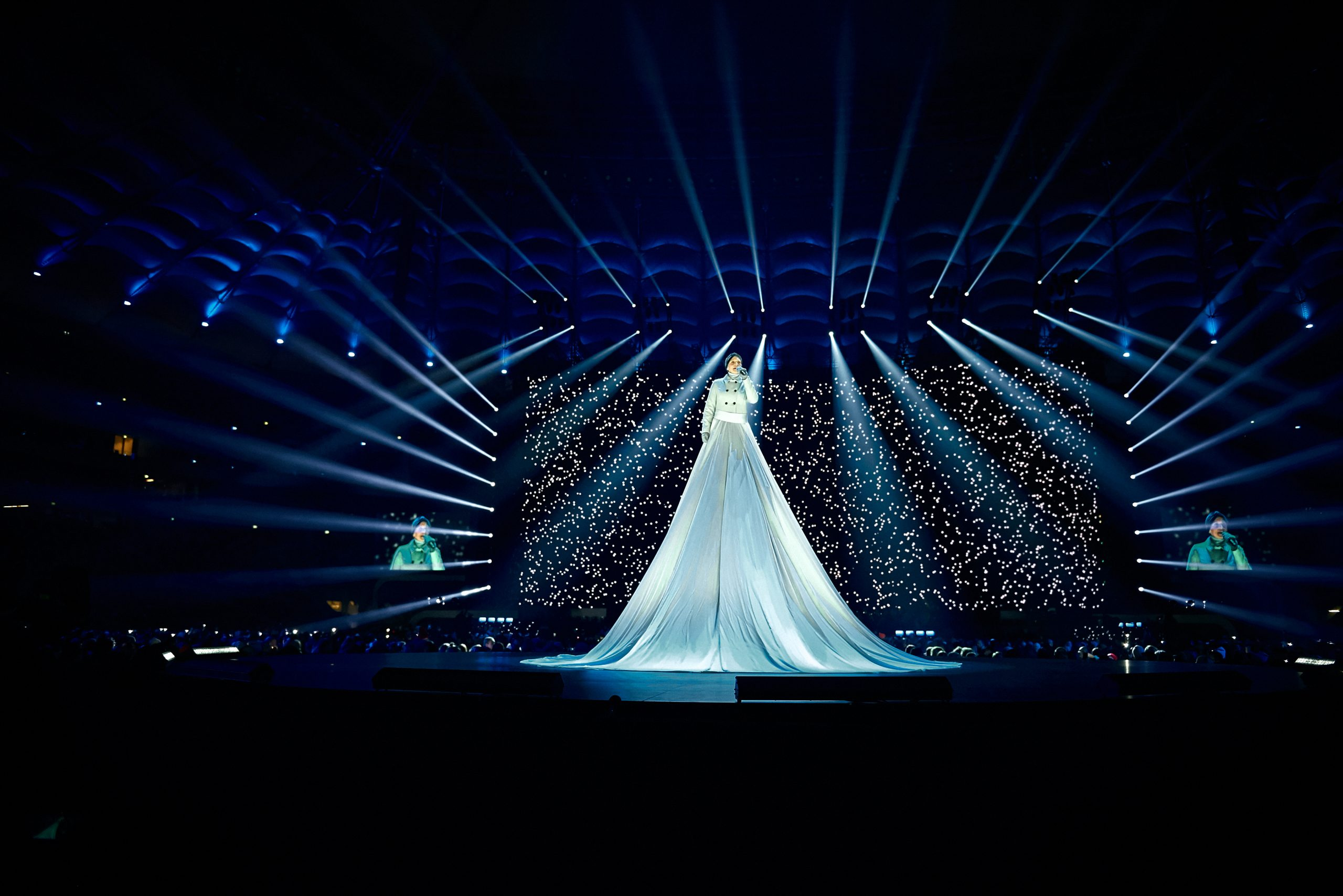 : A performer in a huge bright dress on a raised platform during a performance