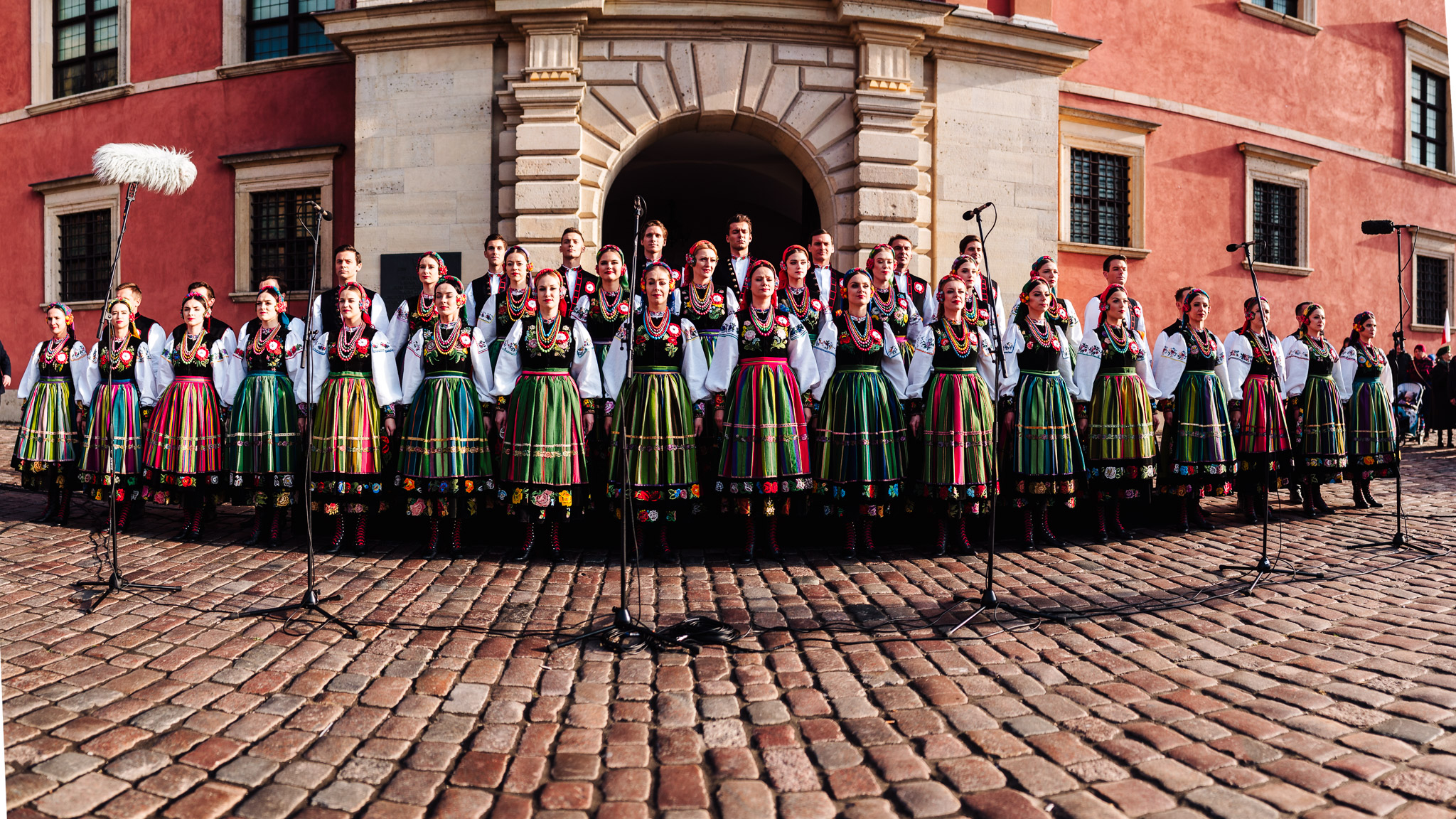Women in folk costumes lined up in front of the Royal Castle in Warsaw, ready to sing the national anthem