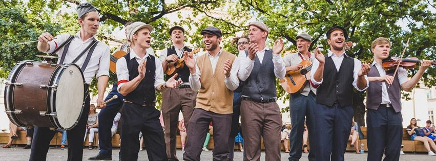 : A group of laughing musicians during an artistic performance in an urban space