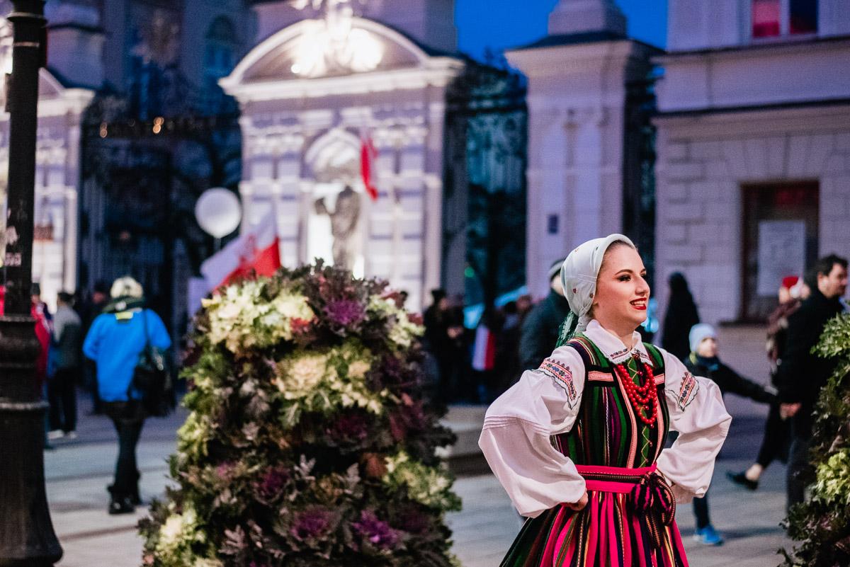 : A woman in a folk costume during an artistic performance in Krakowskie Przedmieście in Warsaw