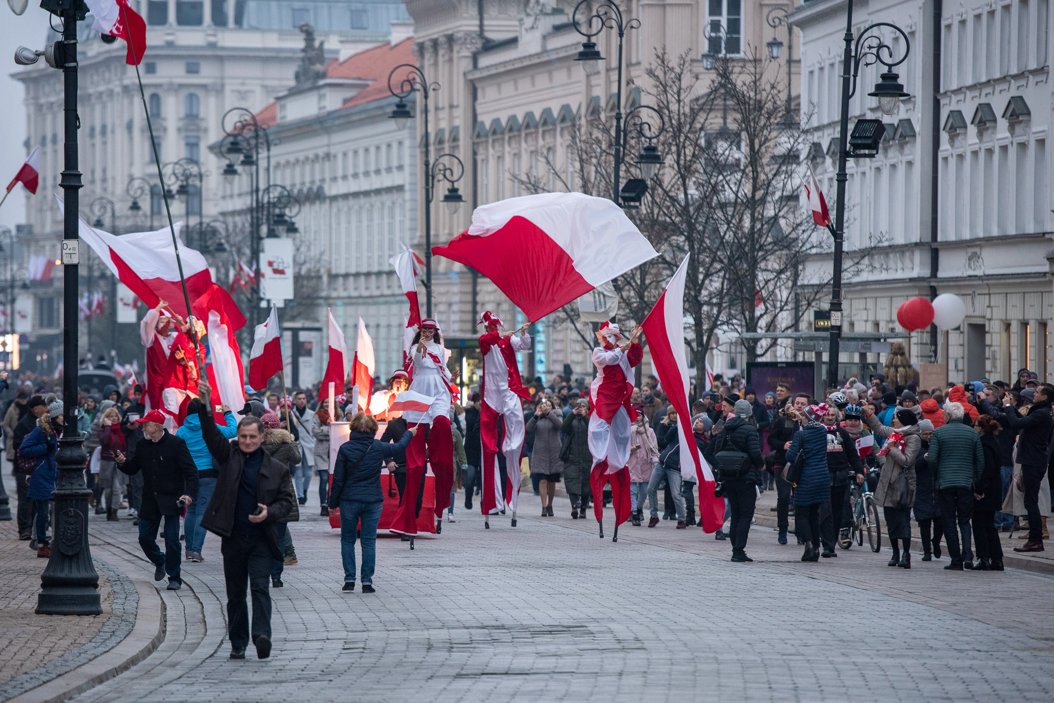 Stilt walkers in red and white costumes marching through the streets, with numerous passers-by watching the spectacle