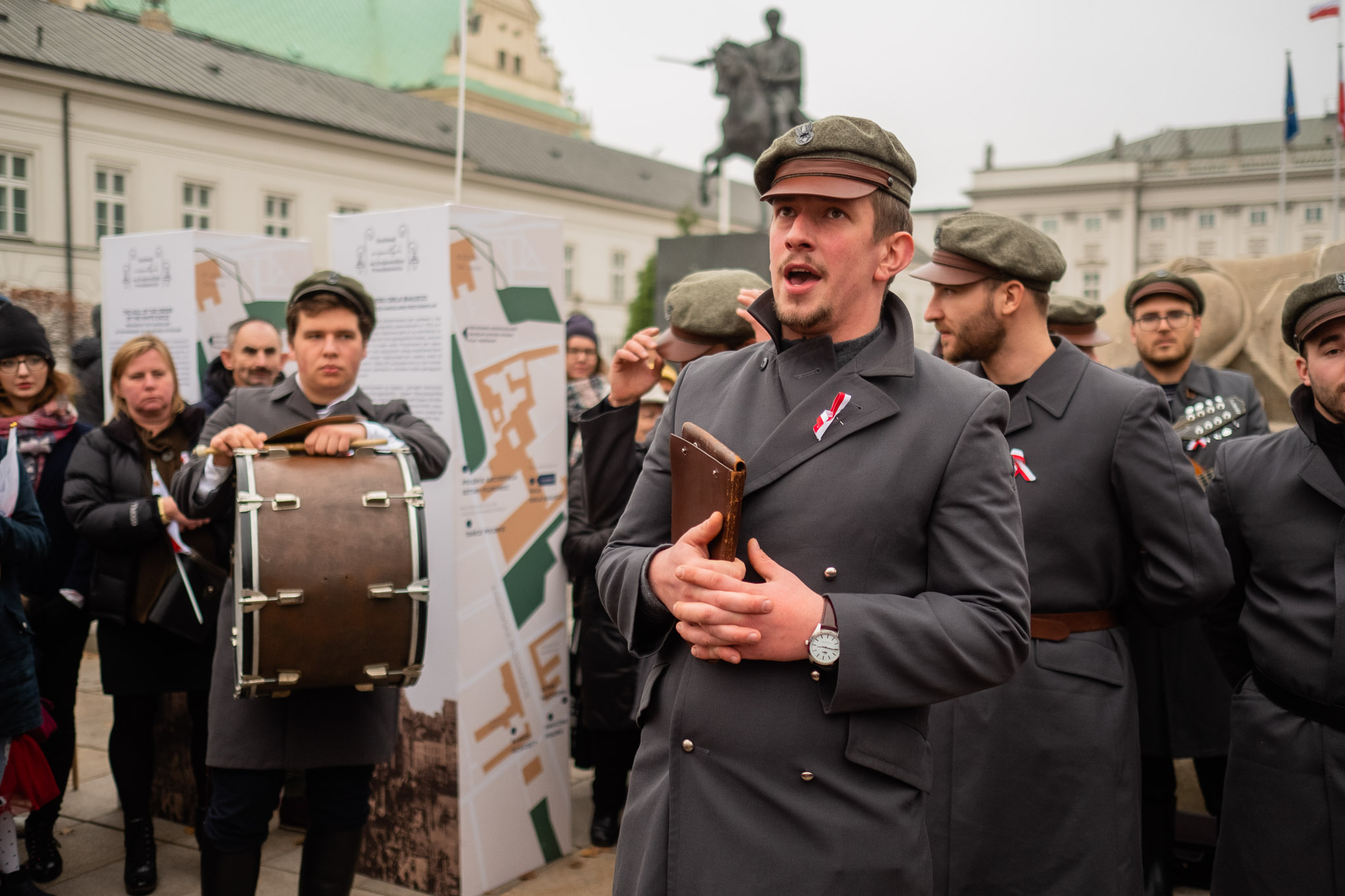 A group of musicians in identical stylised military uniforms during a performance in an urban space