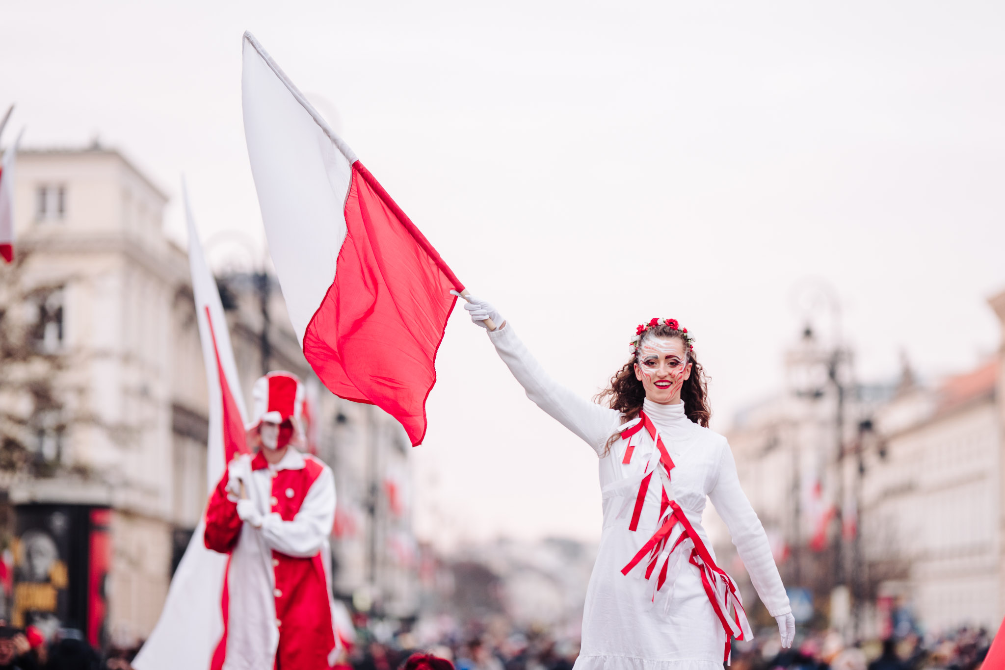 Stilt walkers in red and white costumes marching through the streets; in the foreground, a smiling woman waving a Polish flag.