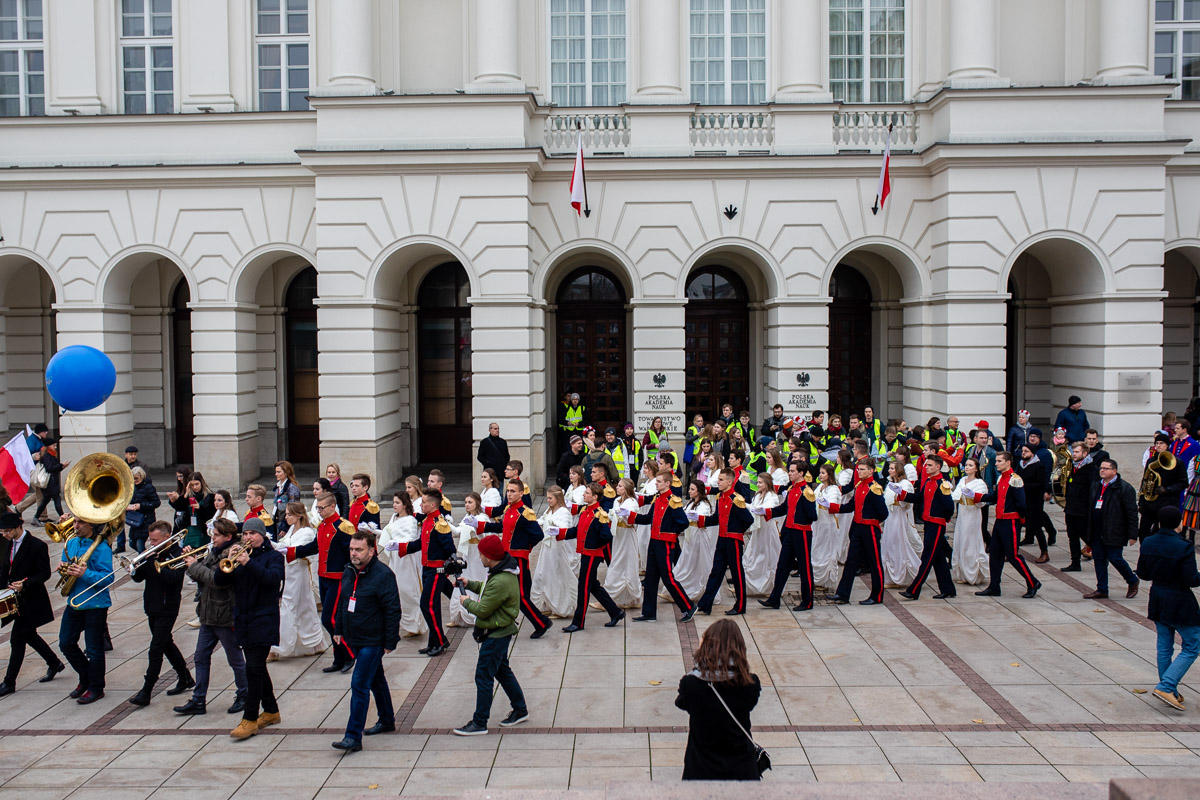 A group of people in festive costumes dancing the polonaise in pairs in the street, accompanied by a band and watched by passers-by