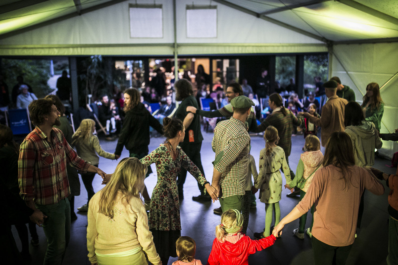 A photograph showing people dancing under a tent. Participants, including children, dance in a circle holding hands; in the background, there is a pavilion and spectators sitting on deck-chairs