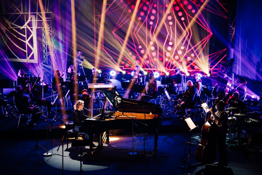 An illuminated stage with musicians, with a grand piano in the foreground