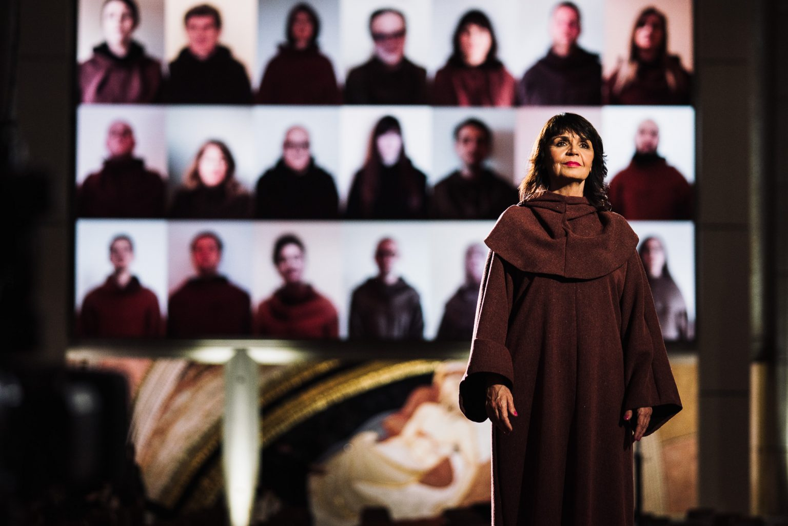 In the foreground, a female performer in a modest dress reminiscent of a nun's frock; in the background, a screen showing members of the choir