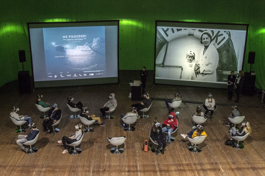 A colour photograph showing people in virtual goggles watching a VR movie. In the background, a still from the film and archival photos from the deck of the MS Piłsudski are displayed on screens.