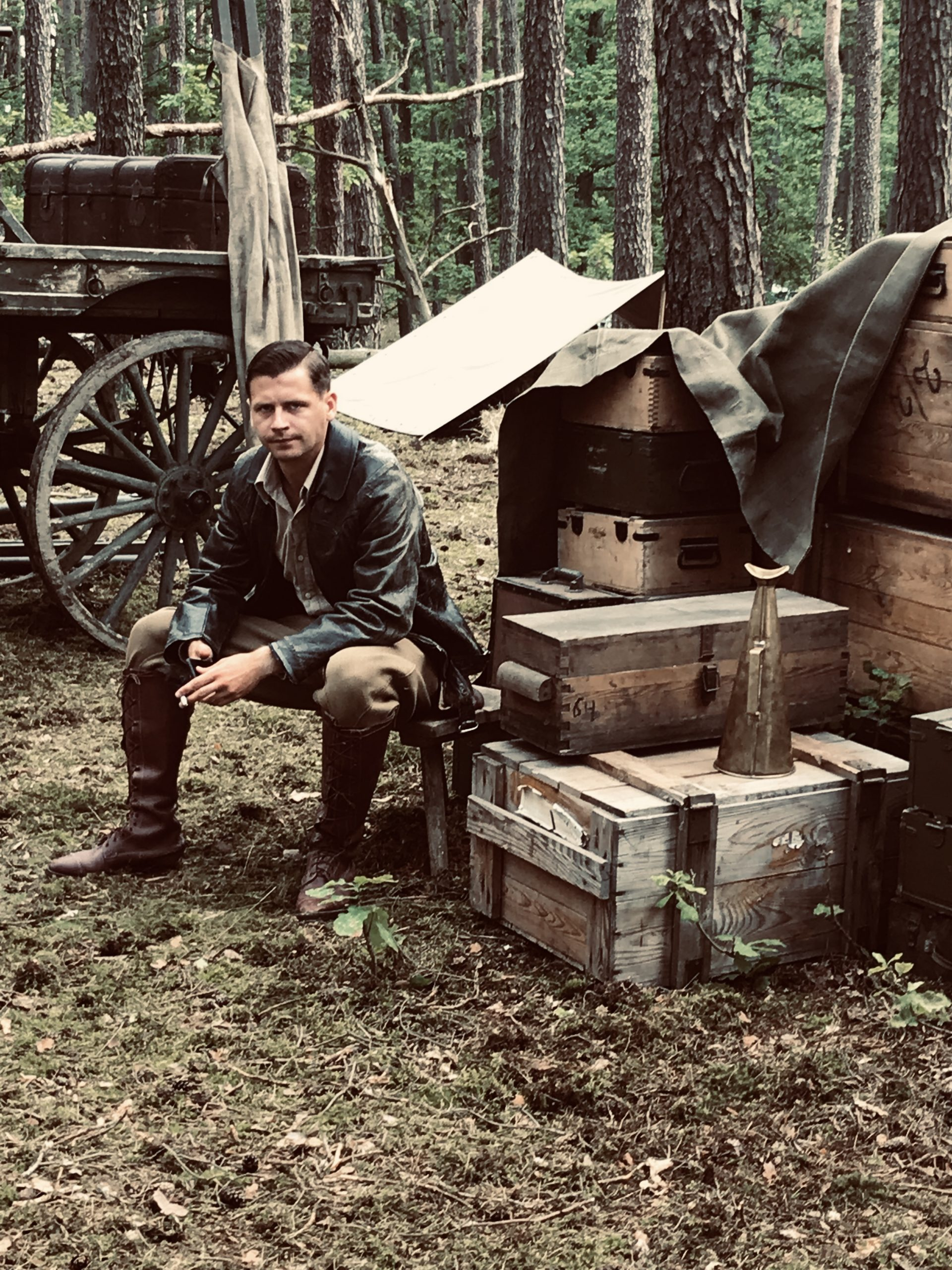 Description: A man in an early 20th century costume sitting in a forest on a stool next to stacked chests; in the background, part of a wagon is visible
