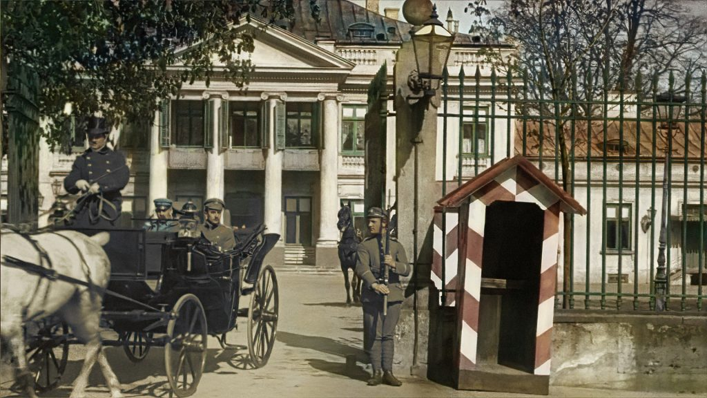 A carriage with two passengers leaving through a guarded gate with a booth; in the background, a building with a colonnade
