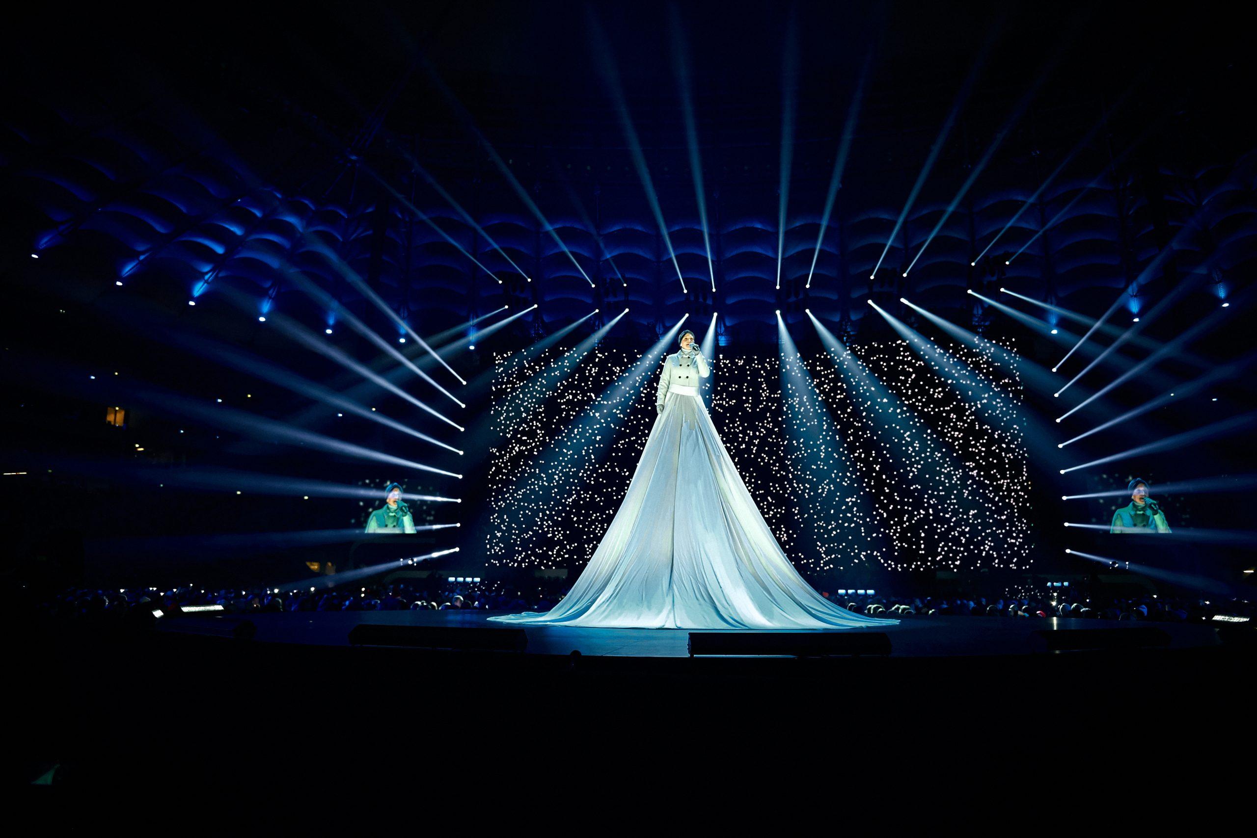 артистка на подмостках в огромном светлом платье во время выступления
