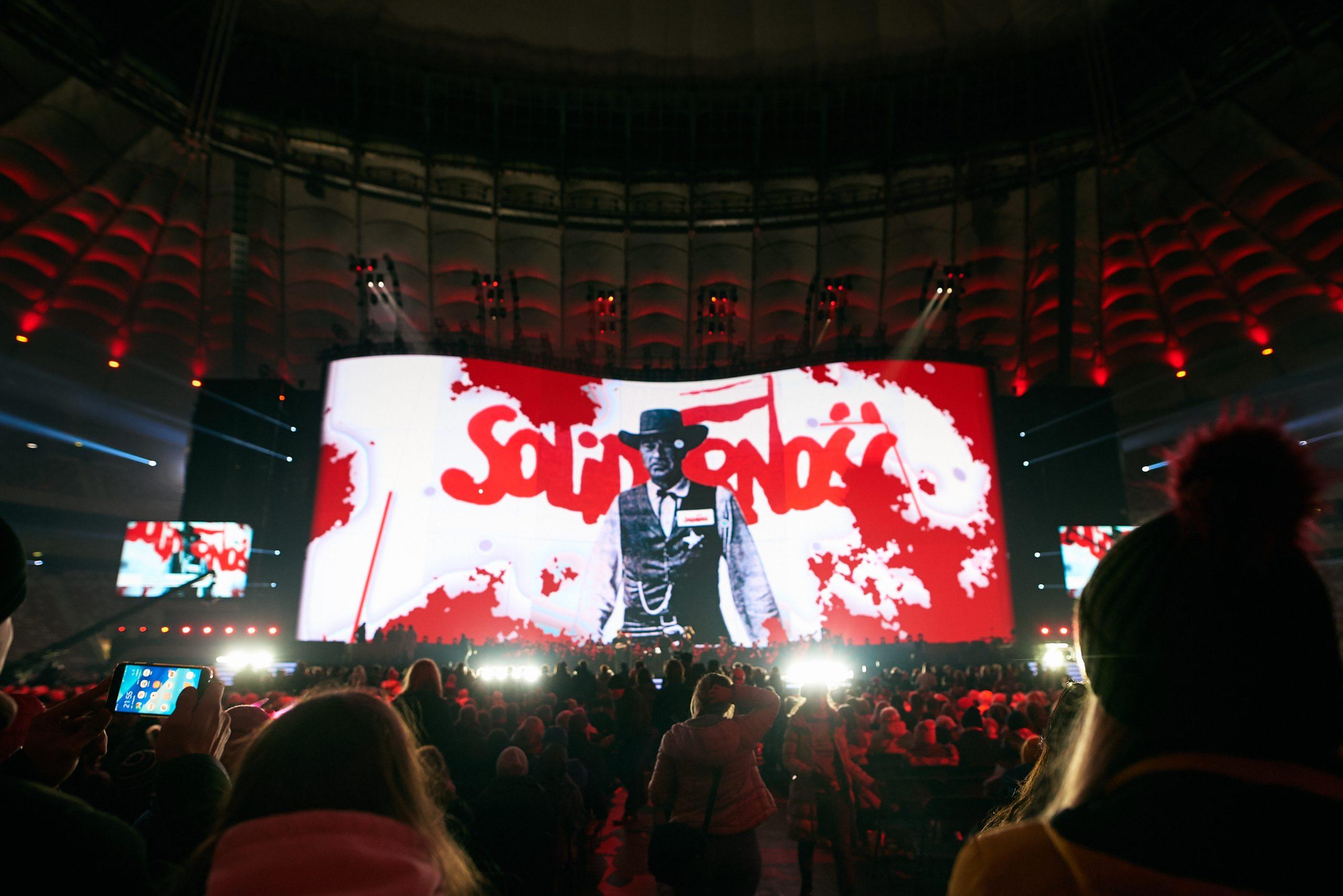 фото с концерта, на котором виден видеоэкран с надписью «Солидарность»
