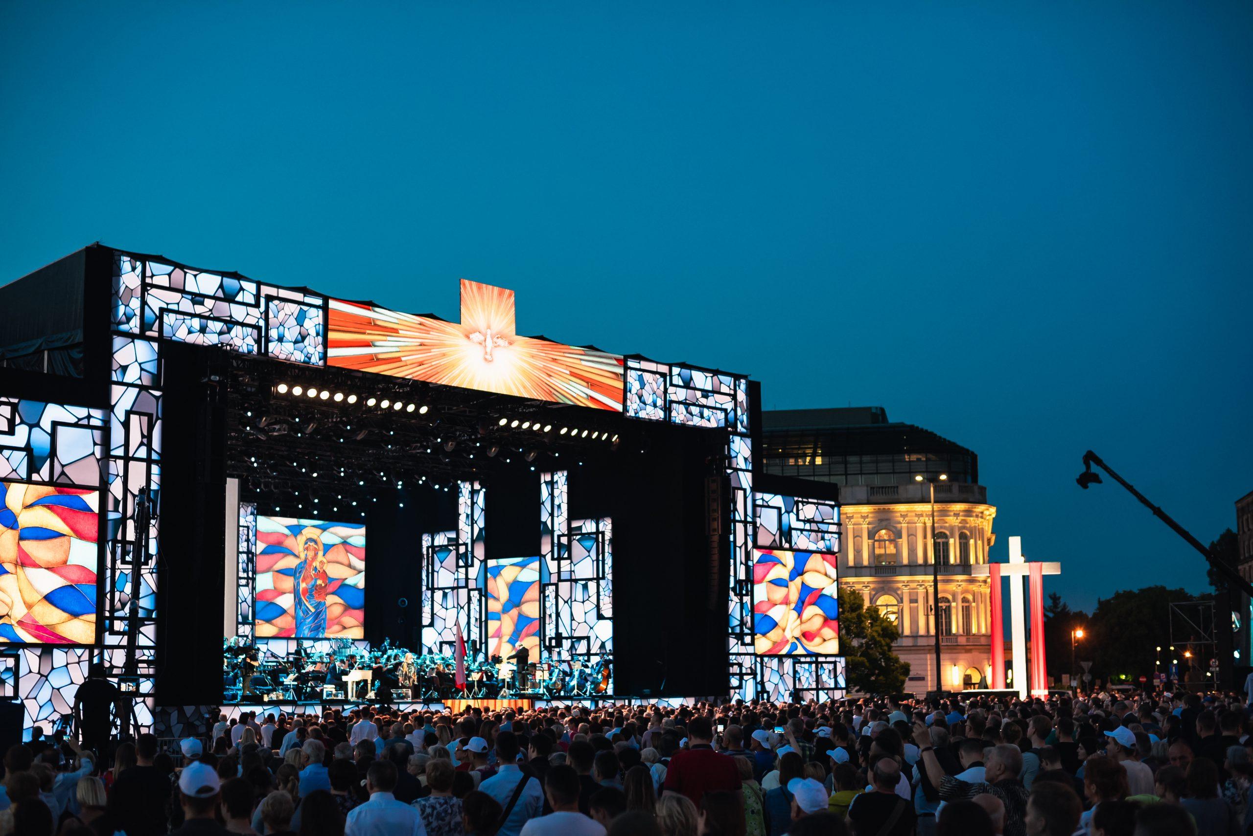 фото, представляющее освещённую сцену во время концерта, окружённую толпой зрителей