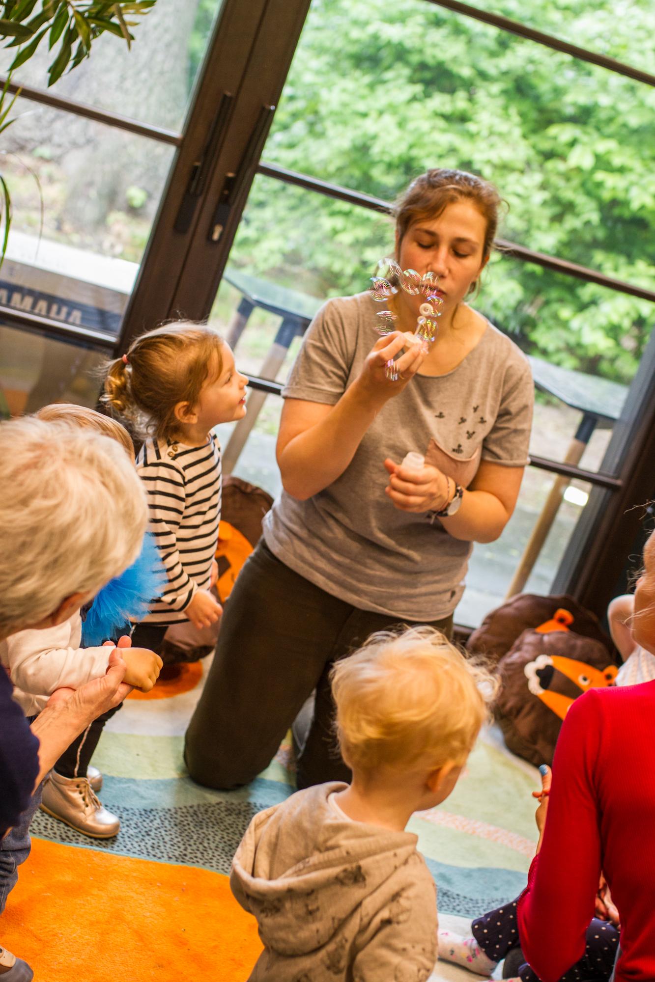 аниматор, пускающая мыльные пузыри во время игры с маленькими детьми. Вокруг неё играющие на коврике дети