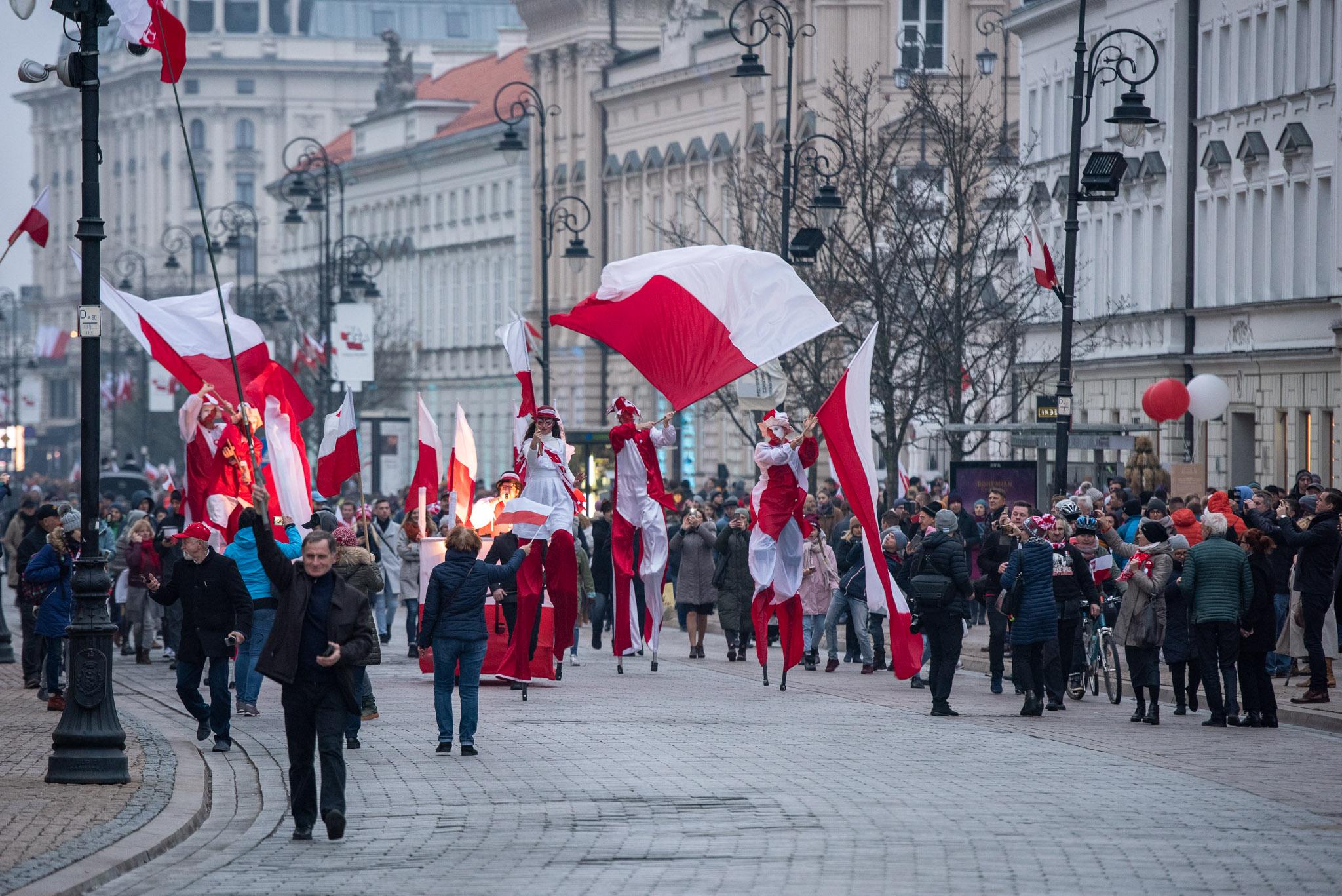 артисты на ходулях, марширующие по улицам в бело-красных костюмах, вокруг толпа прохожих, наблюдающих за представлением