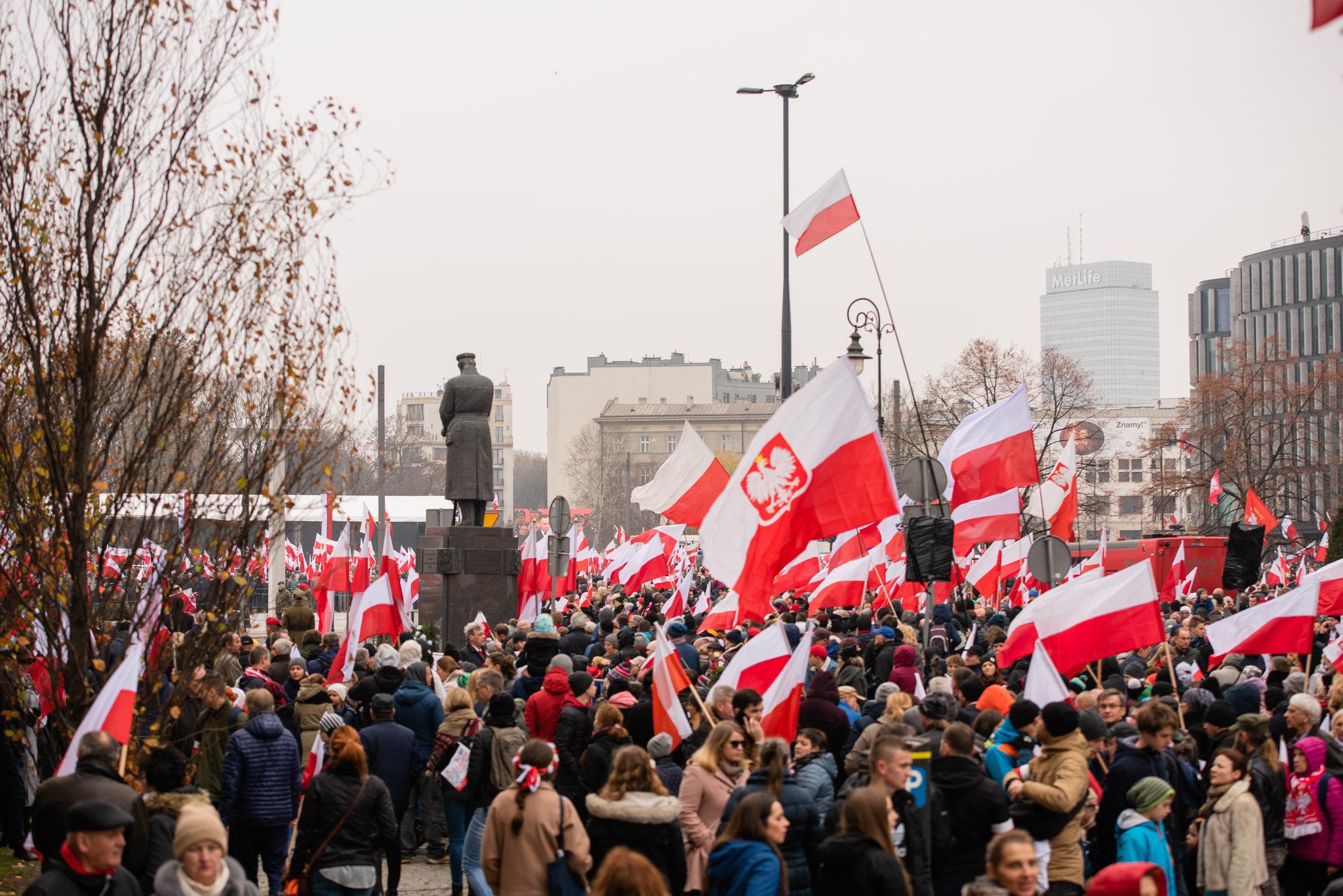толпа людей с польскими национальными флагами, на заднем плане памятник маршалу Юзефу Пилсудскому