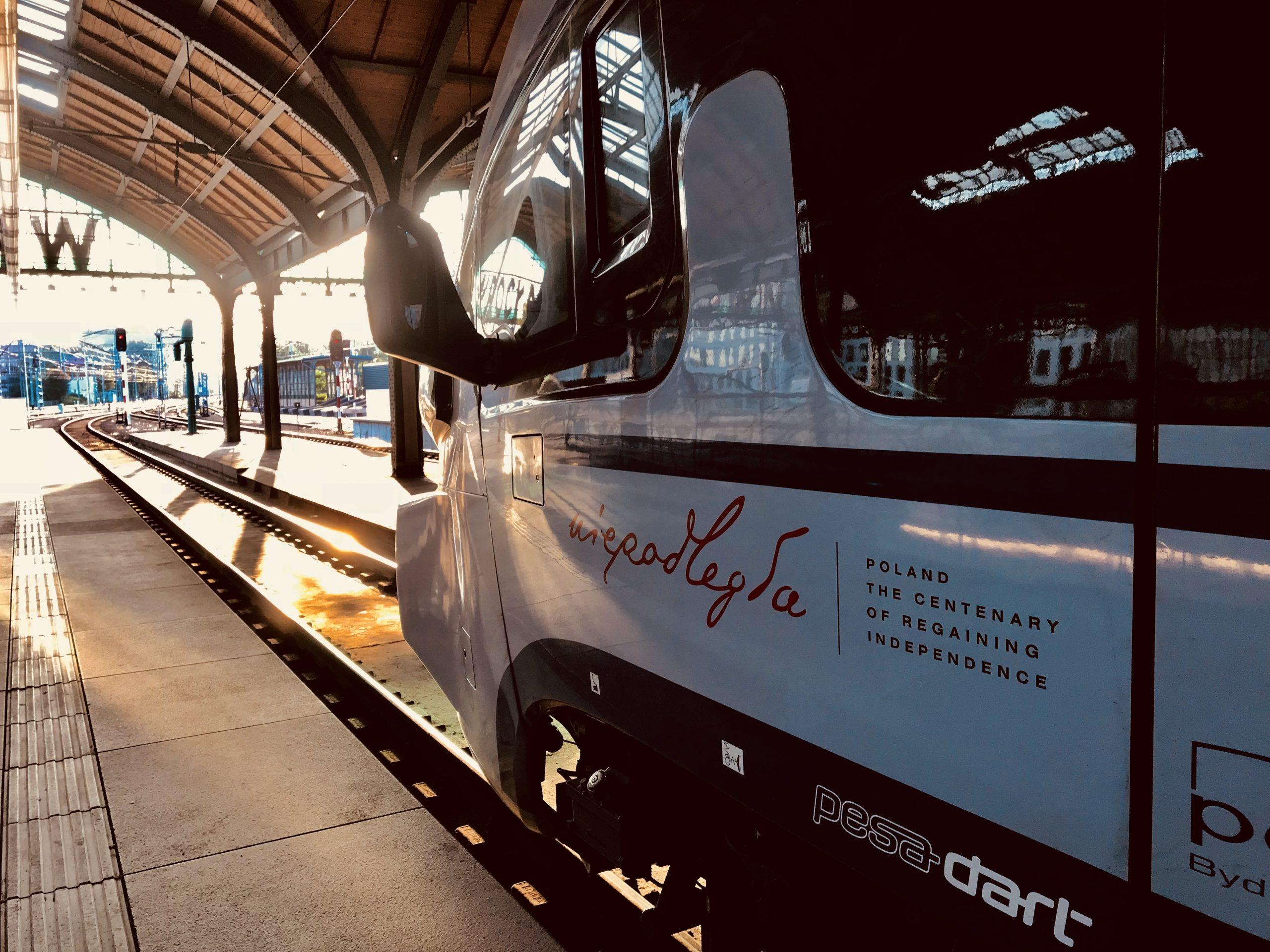 голова поезда с логотипом «Независимая». Поезд стоит на станции на фоне заходящего солнца