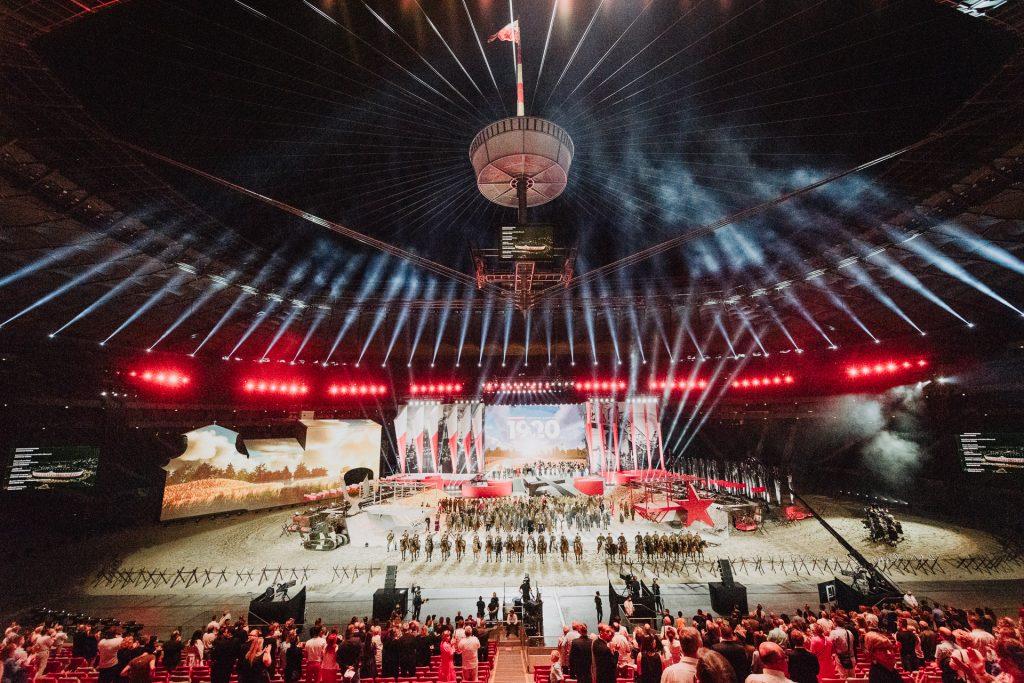 огромная сцена с большим количеством декораций. На сцене множество артистов во время представления. В верхней части фотографии купол Национального стадиона, в нижней части – кресла и зрители