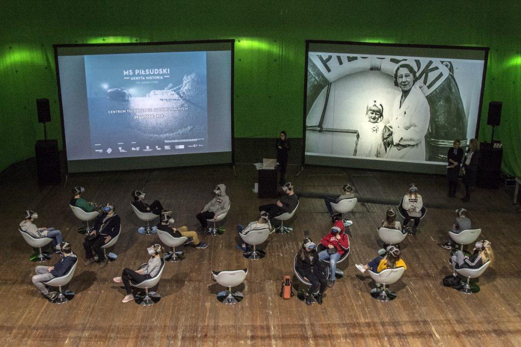 цветная фотография, представляющая людей в виртуальных очках, смотрящих фильм в VR-технологии. На заднем плане снимок из фильма иархивная фотография «М.С. Пилсудского», проецируемые с проектора