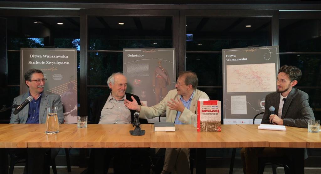 трое улыбающихся мужчин постарше, беседующих за столом. Справа мужчина помладше – модератор дискуссии На заднем плане – планшетная выставка, посвящённая Варшавской битве 1920 года