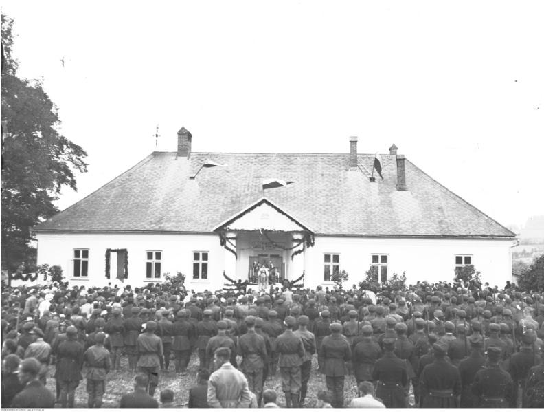 Uroczystość odsłonięcia tablicy pamiątkowej z okazji 20-lecia Szkoły Strzeleckiej w Stróży. Msza polowa. Widoczna elewacja budynku szkolnego. Źródło: NAC