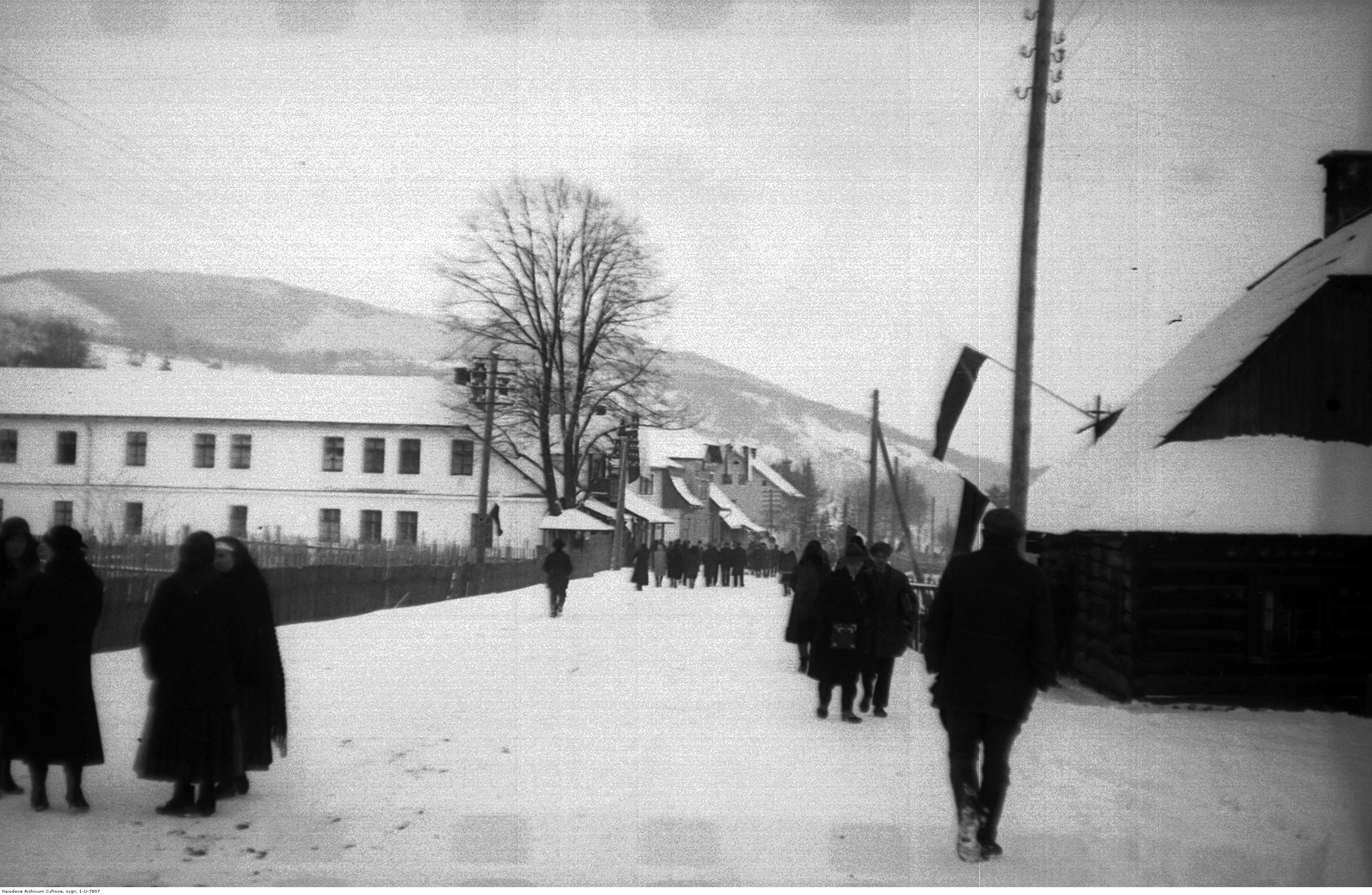 Fragment miejscowości Wisła. Fragment jednej z ulic miejscowości. Widoczni piesi. Fotografia wykonana zimą. Źródło: NAC.