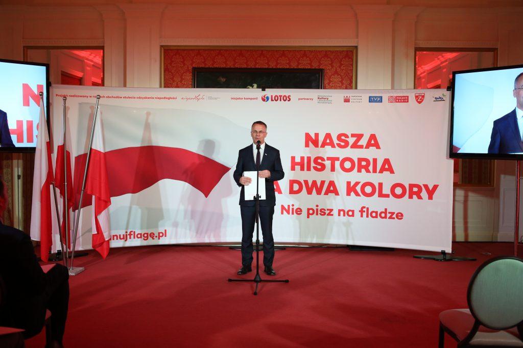 mężczyzna elegancko ubrany stoi na środku przed mikrofonem, w tle baner z flagą Polski i hasłem kampanii