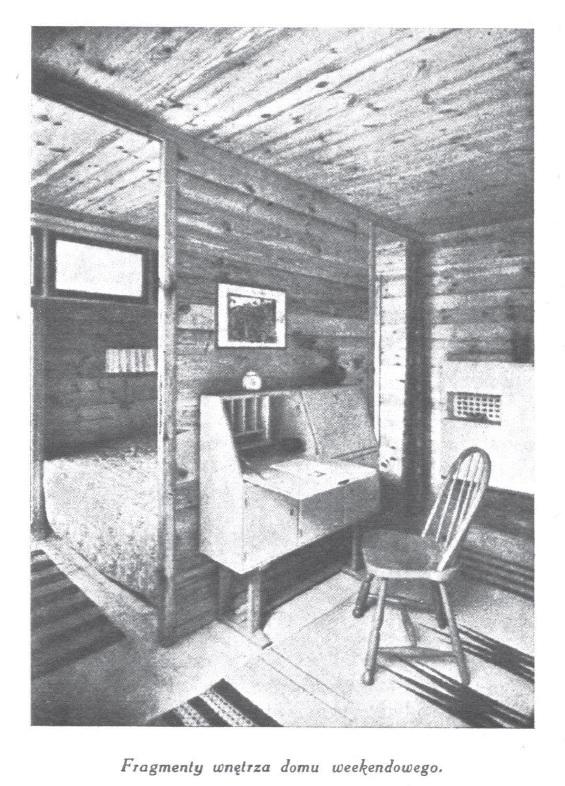 Fragmenty wnętrza domu weekendowego, widoczne składane biurko i krzesło, w tle oddzielona ścianką sypialnia