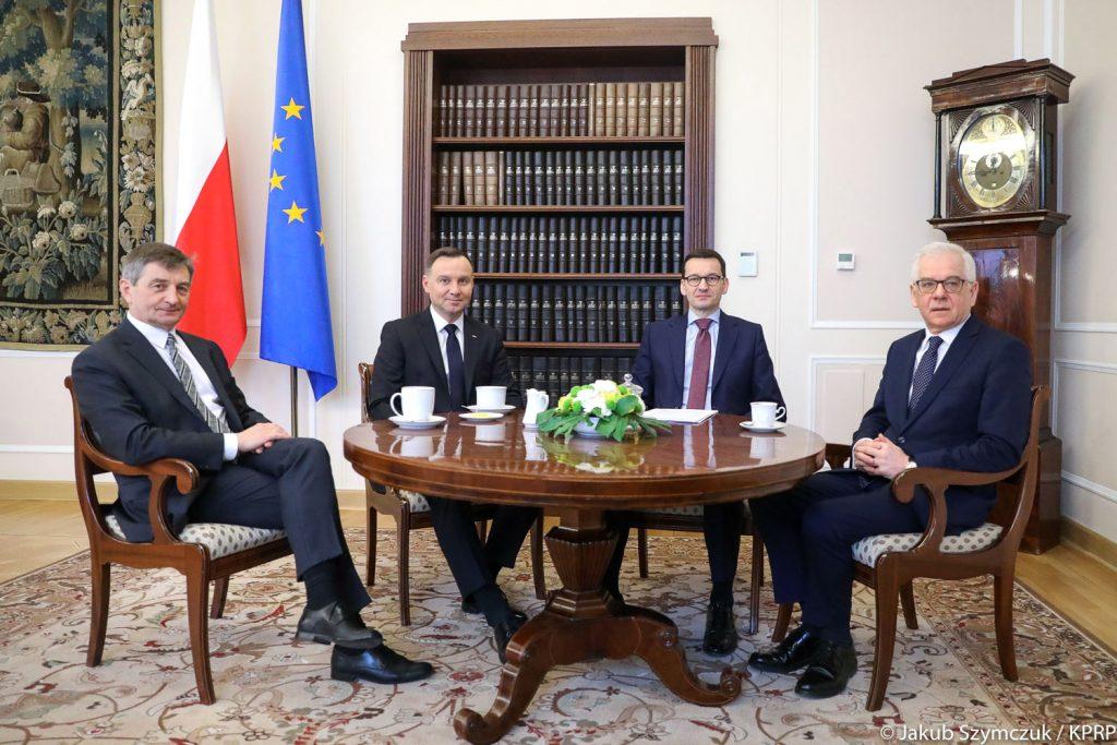 czterech mężczyzn siedzi przy okrągłym stole w oficjalnym gabinecie, pod ścianą dwie flagi, po lewej polska, po prawej unii europejskiej