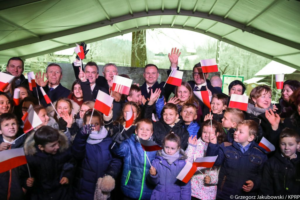 grupka kilkudziesięciu dzieci macha małymi flagami, w ostatnim rzędzie stoi prezydent duda