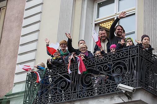 grupka osób na balkonie budynku, dzieci i dorośli, machają i się cieszą, zawieszone są polskie flagi