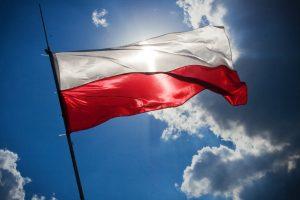 Czerwono-biała flaga Polski na tle błękitnego nieba