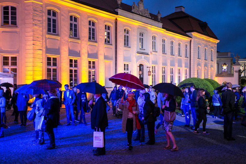 grupa ludzi stoi przed kolorowo oświetlonym pałacem, w rękach mają parasolki i torby, kręcą się i oglądają