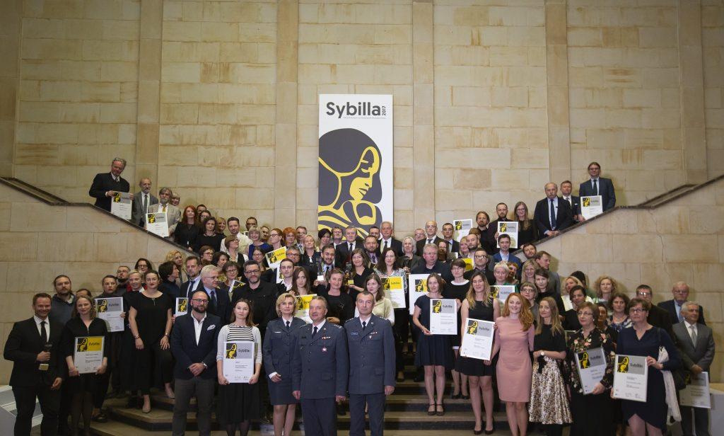 na schodach stoi grupa laureatów trzymając w rękach dyplomy i wyróżnienia