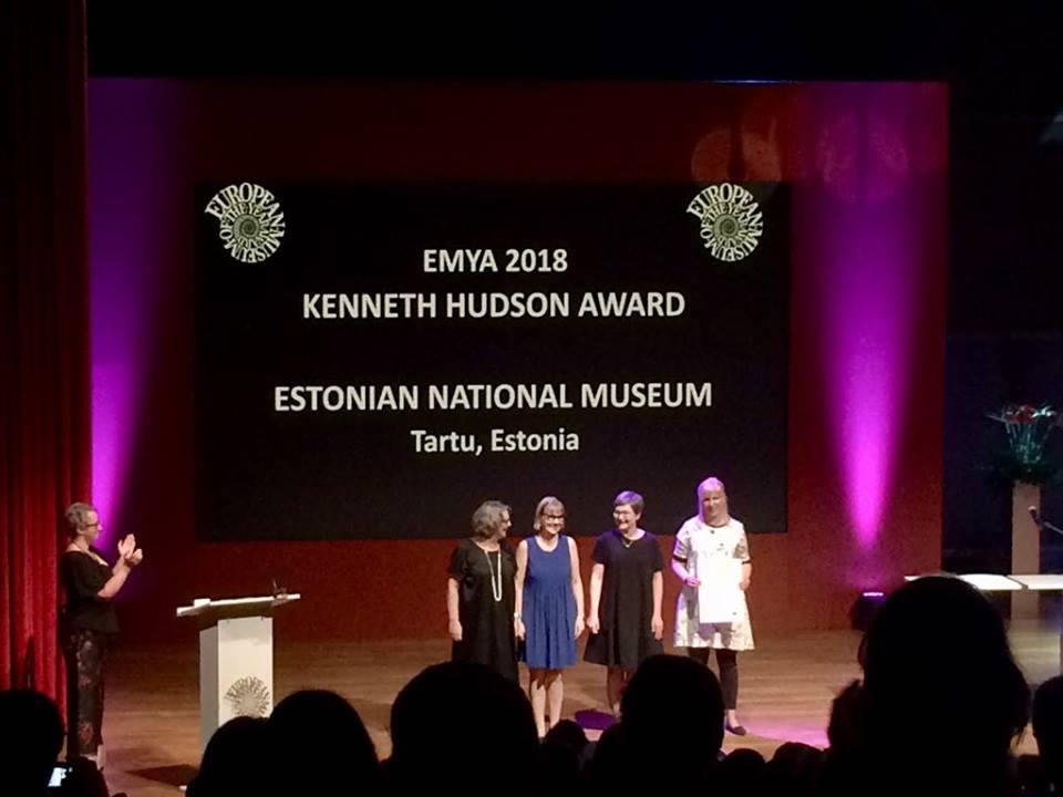 czworo ludzi na podium, prezentują odbieraną nagrodę, w tle napis opisujący muzeum