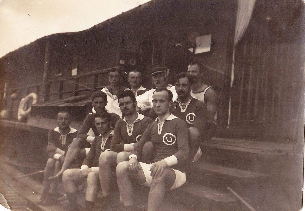 grupa mężczyzn siedzących na drewnianych stopniach
