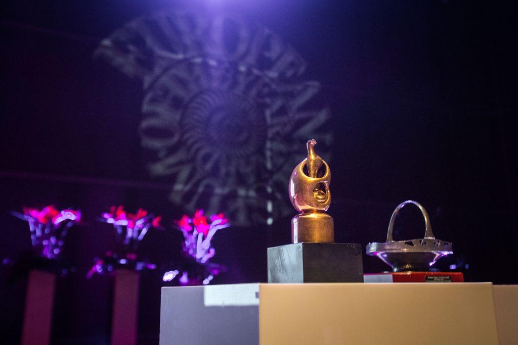 złota statuetka, fioletowe tło ze znakiem emya