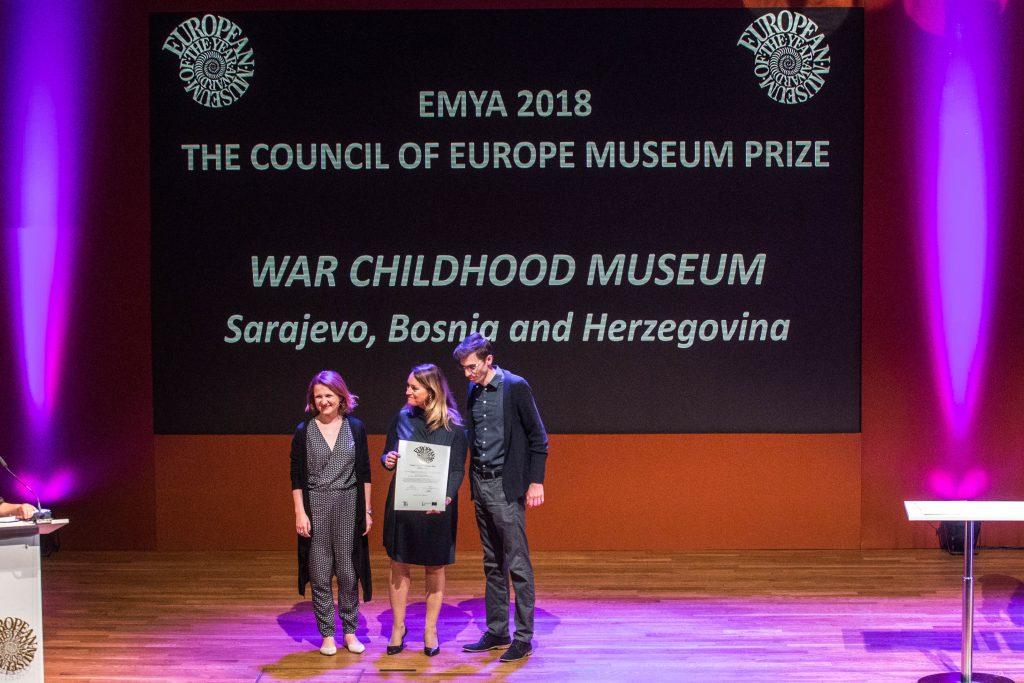 troje ludzi na podium, prezentują odbieraną nagrodę, w tle napis opisujący muzeum