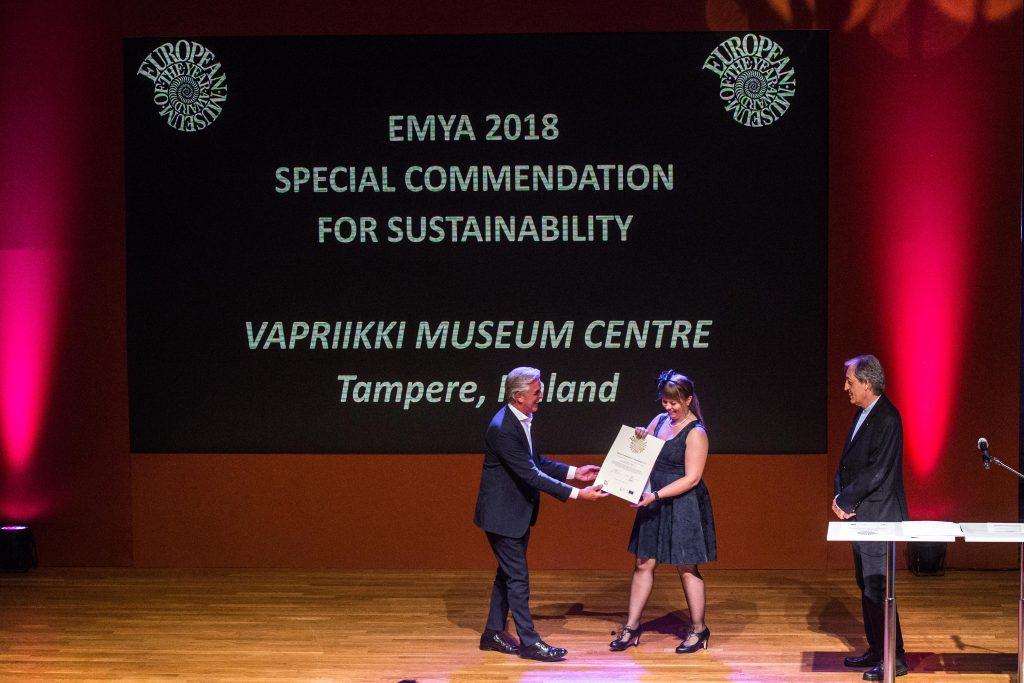 dwoje ludzi na podium, prezentują odbieraną nagrodę, w tle napis opisujący muzeum