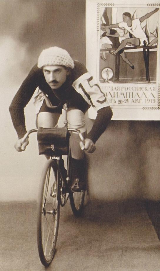 kolarz z wąsem i w kasku na rowerze w studiu fotograficznym, z plakatem olimpiady na ścianie