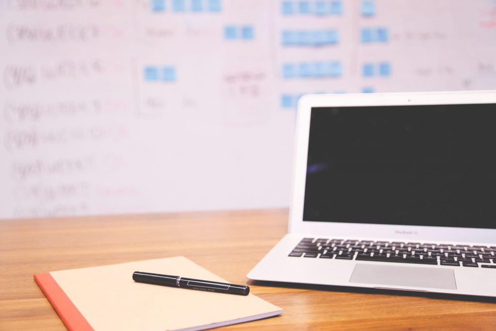komputer stojący na biurku z tablicą w tle