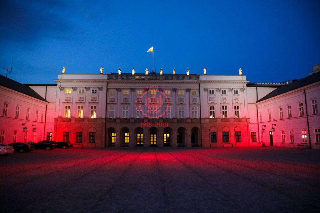 klasycystyczny pałac podświetlony na biało-czerwono, na środku fasady symbol prezydenckich obchodów