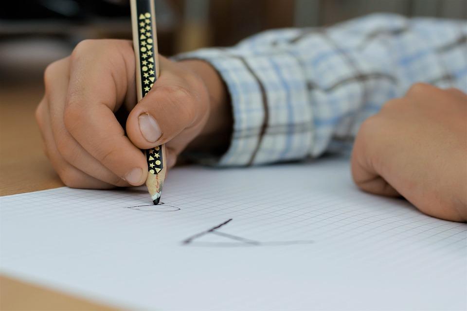 ręce chłopca, przed nim kartka z zapisaną literką A ołówkiem, który trzyma w ręku