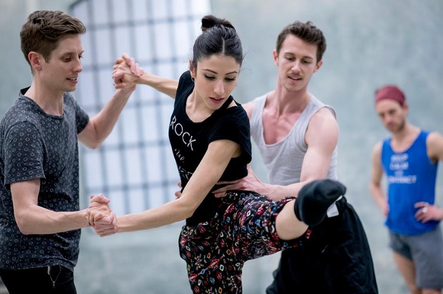 Trójka młodych ludzi ćwiczy taniec, dwaj mężczyźni przytrzymują kobietę, która unosi nogę z obciągniętymi palcami