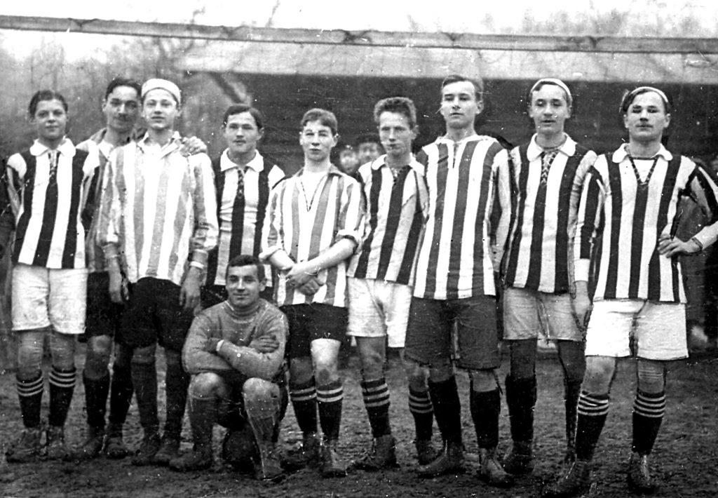 grupa dziesięciu mężczyzn w krótkich spodenkach i koszulach w biało-czarne paski
