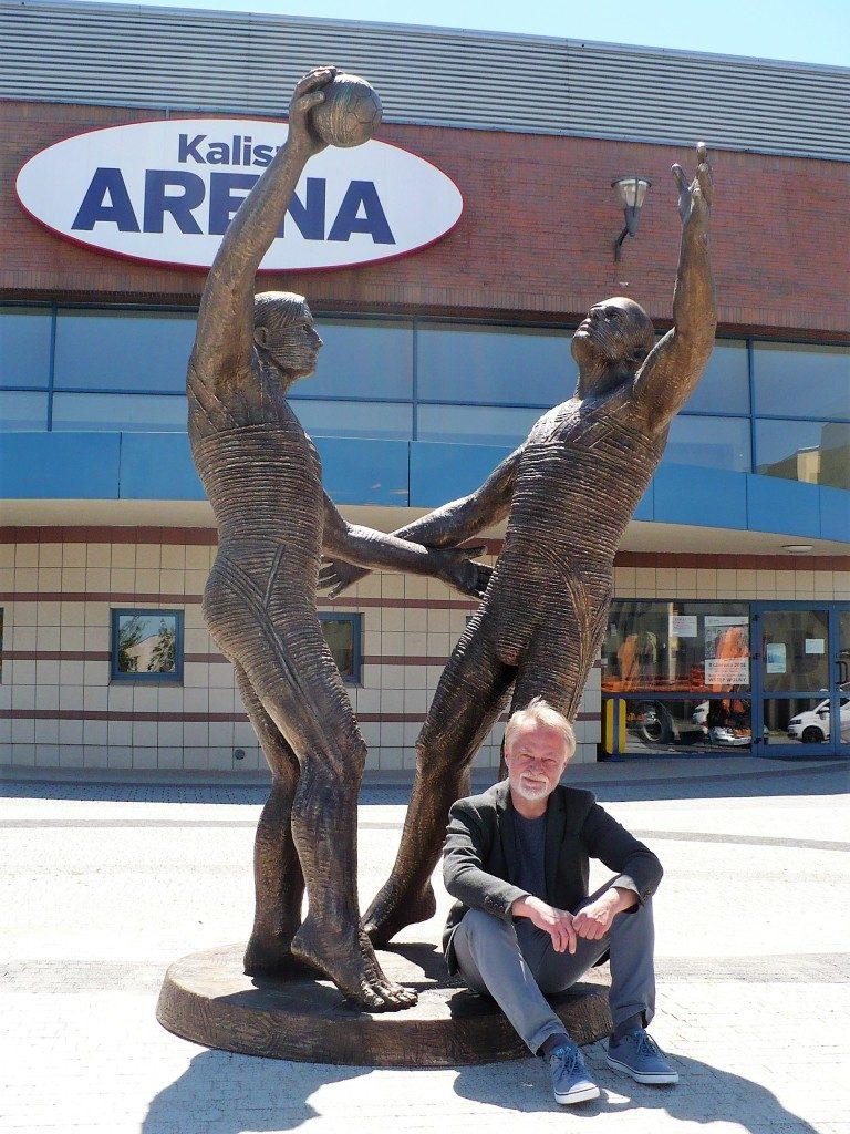 brązowa rzeźba dwóch szczypiornistów sprzed stu lat, u jej stub siedzi starszy pan rzeźbiarz, w tle kaliska arena