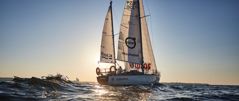 jacht na morzu w promieniach zachodzącego słońca