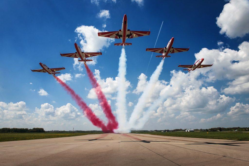 5 startujących samolotów, zostawia za sobą kolorowe ogony, 3 białe, 2 czerwone