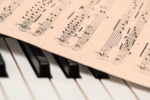 kartka z uwerturą na klawiszach fortepianu