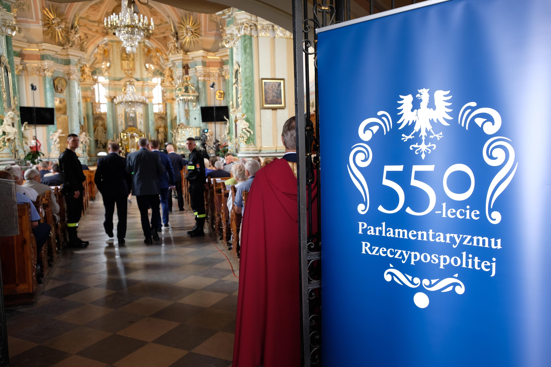 wejście do kościoła, po prawej logo obchodów 550-lecia polskiego parlamentaryzmu